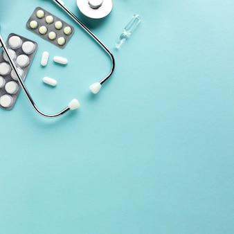 Estetoscopio con blíster medicamentos contra el fondo azul.