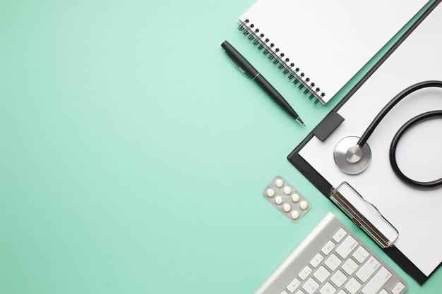 Estetoscopio y blister de píldora con material de oficina sobre fondo verde