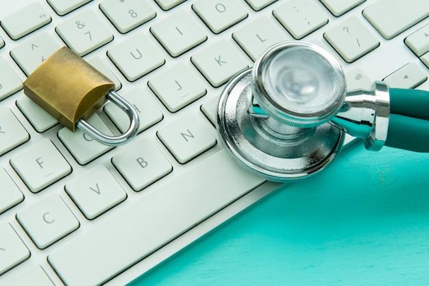 Estetoscopio y candado en un teclado sobre fondo azul.