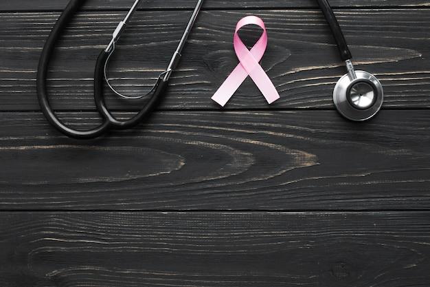 Estetoscopio y cinta rosada en la mesa oscura