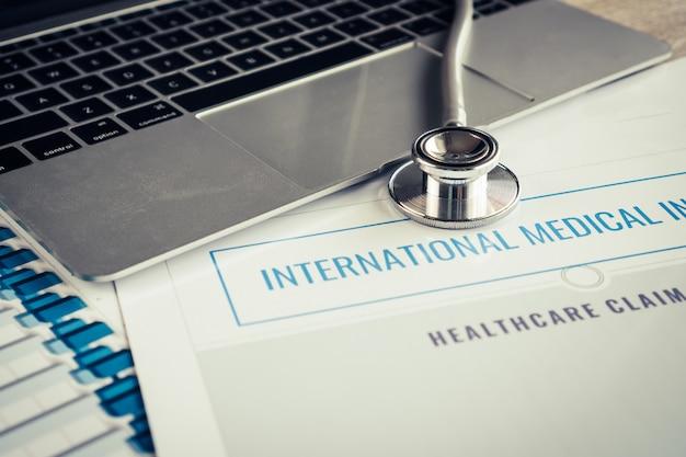 Estetoscopio en computadora con formularios de reclamo de seguro médico internacional