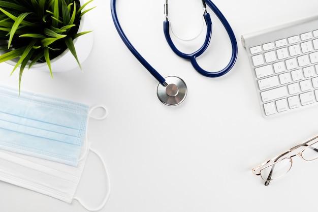 Estetoscopio, computadora y máscaras protectoras sobre una mesa blanca de un médico.