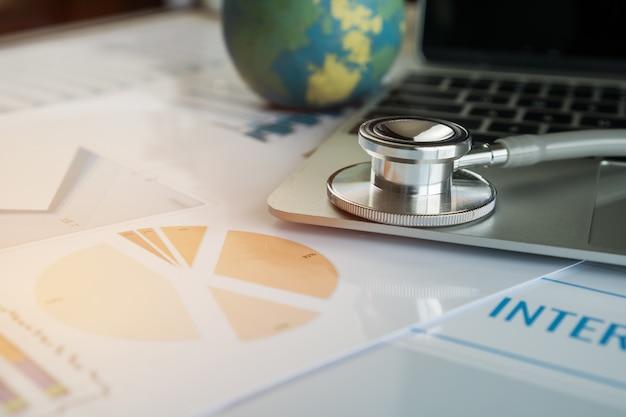 Estetoscopio en computadora con seguro médico internacional, formularios de reclamo de atención médica