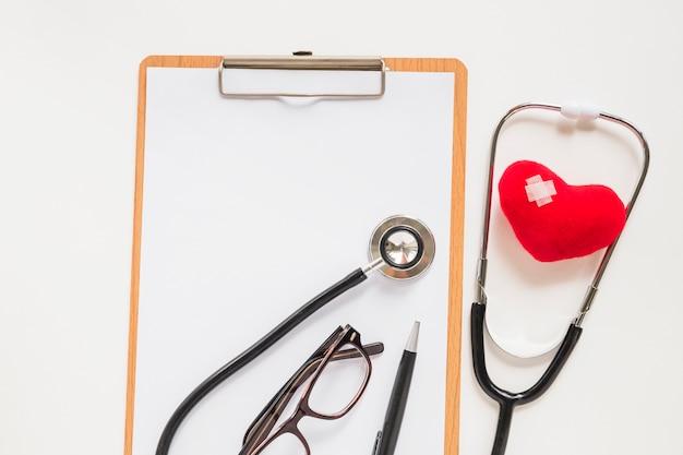 Estetoscopio con corazón rojo relleno con vendaje en portapapeles
