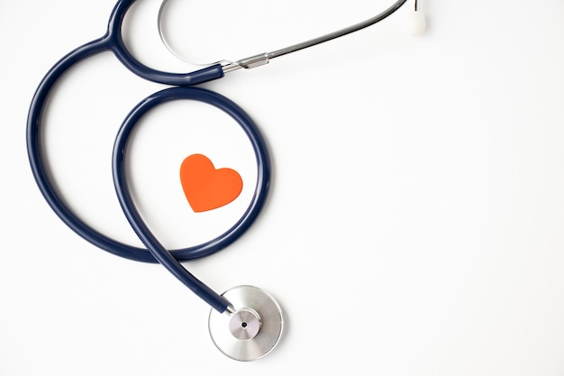 Estetoscopio con corazón rojo aislado sobre fondo, vista superior. concepto de salud y medicina