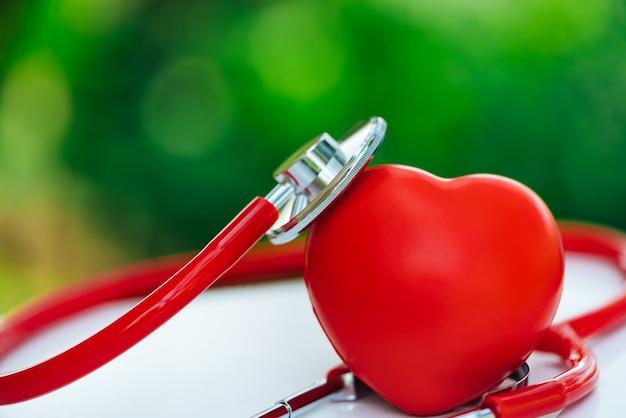 Un estetoscopio y un corazón rojo en fondos verdes de un bokeh.
