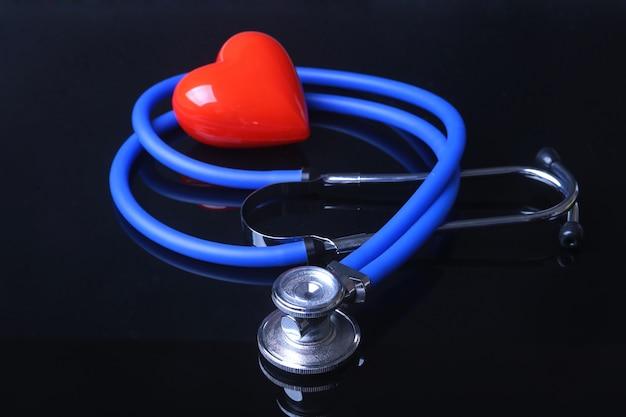 Estetoscopio, corazón rojo y medidor de presión arterial sobre fondo negro espejo.