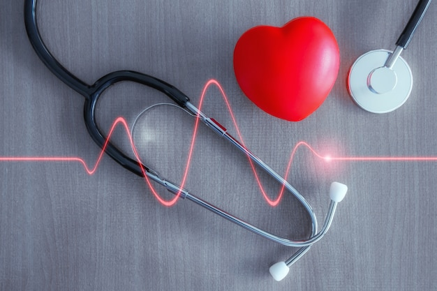 Estetoscopio y corazón rojo con onda de corazón rojo brillante.