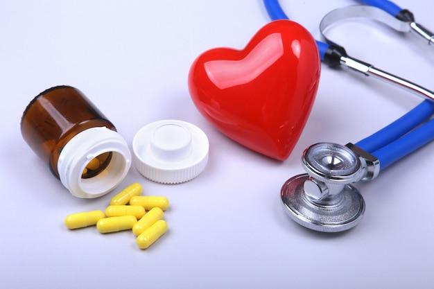 Estetoscopio, corazón rojo y pastillas surtidas.