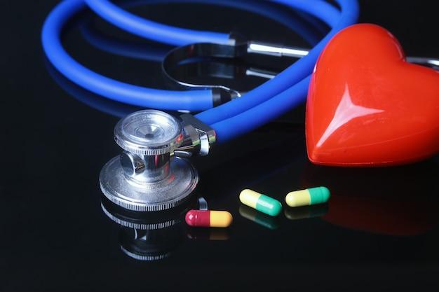 Estetoscopio, corazón rojo y pils surtidos.