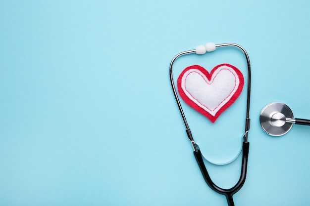Estetoscopio y corazón sobre un fondo azul. salud y medicina