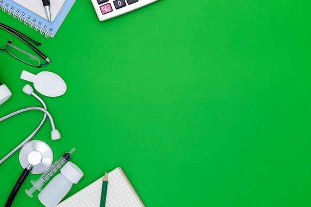 Estetoscopio con cuaderno, bolígrafo, papel blanco, gafas, botella de medicamento, jeringa de alimentación sobre fondo verde con copyspace