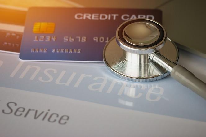 Estetoscopio en mock up tarjeta de crédito con número en el titular de la tarjeta en la oficina del hospital