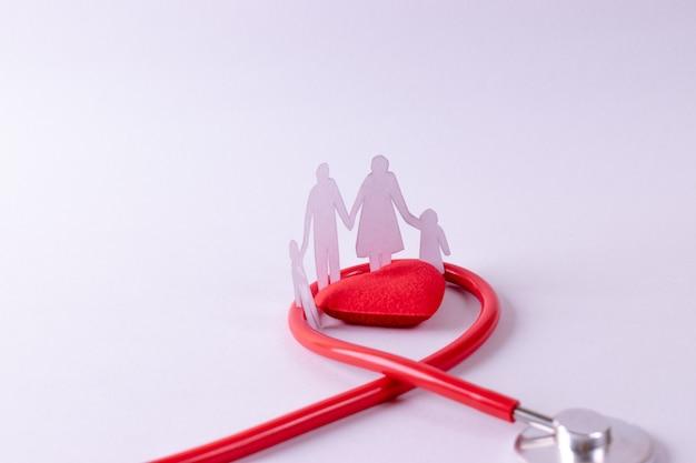 Estetoscopio envuelto alrededor de corazón rojo y figura familiar en papel blanco