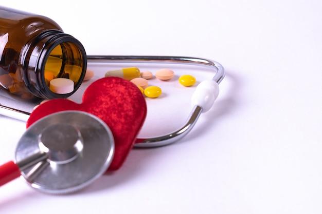 Estetoscopio envuelto alrededor de corazón rojo y la mezcla de color tabletas de pastillas de drogas