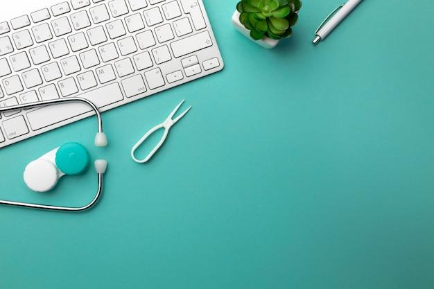 Estetoscopio en escritorio de doctores con teclado, lentes y lentes de contacto