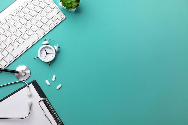 Estetoscopio en el escritorio del médico con cuaderno, bolígrafo, teclado, reloj despertador y pastillas