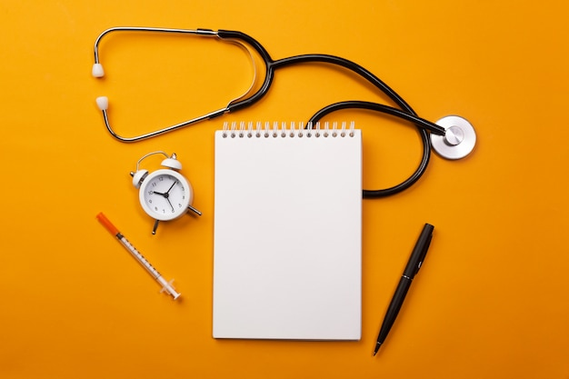 Estetoscopio en el escritorio del médico con cuaderno, reloj despertador y pastillas