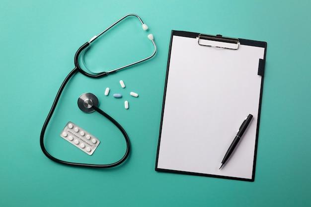 Estetoscopio en el escritorio del médico con tableta, bolígrafo y pastillas