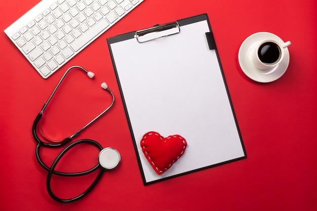 Estetoscopio en el escritorio del médico con tableta, corazón y taza de café