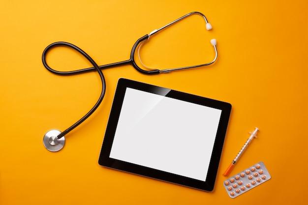 Estetoscopio en el escritorio del médico con tableta digital, jeringa y pastillas