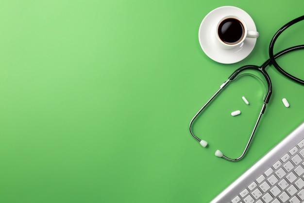 Estetoscopio en el escritorio del médico con taza de café, teclado y pastillas
