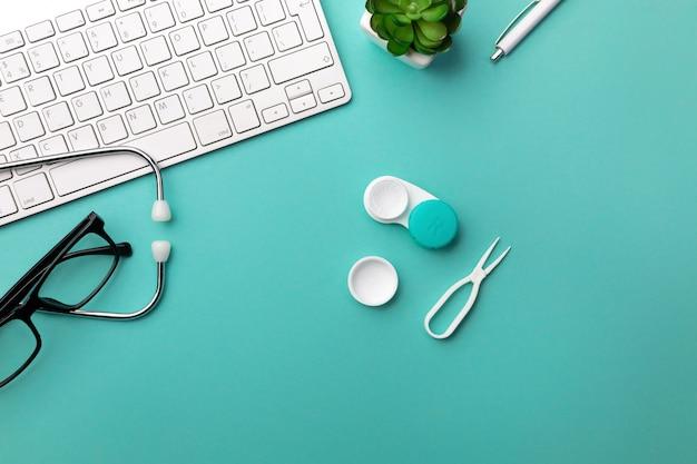 Estetoscopio en el escritorio del médico con teclado, lentes y lentes de contacto