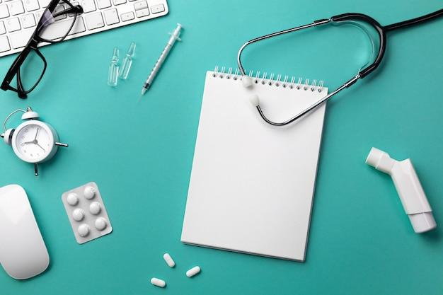 Estetoscopio en el escritorio del médico con teclado, reloj despertador, gafas, inhalador, jeringa, ampollas, inhalador y píldoras.