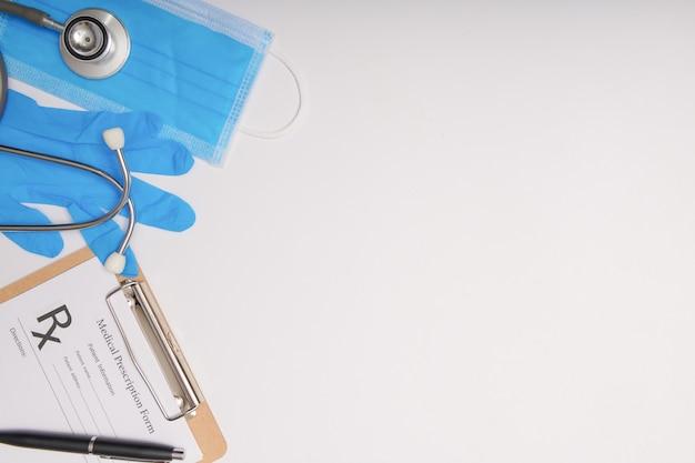 Estetoscopio en el escritorio de los médicos, concepto médico. coronavirus (covid-19. estetoscopio, anteojos y mascarilla en el escritorio blanco. protección contra virus, coronavirus, gripes, resfriados, enfermedades. vista superior plana