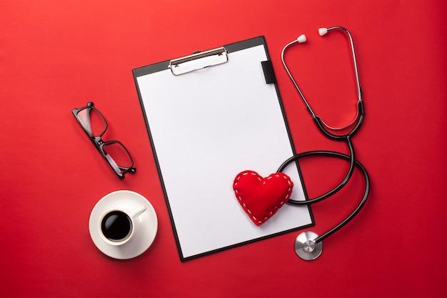 Estetoscopio en el escritorio de los médicos con tableta, corazón y taza de café, vista superior