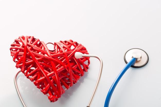 Estetoscopio escuchando corazón decorativo rojo sobre mesa blanca
