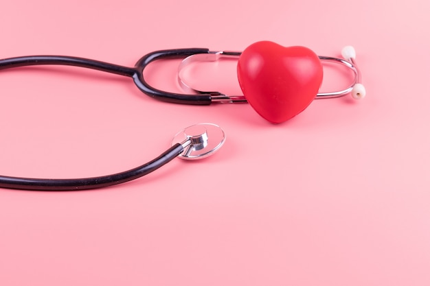Estetoscopio con forma de corazón rojo en rosa. cuidado de la salud, seguro de vida, día mundial del corazón y concepto de cáncer