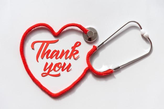 Estetoscopio formando corazón con su cordón. gracias doctor y equipo de enfermeras y personal médico. concepto de salud.