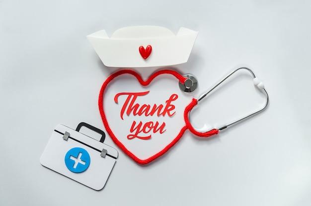 Estetoscopio formando corazón con su cordón. gracias doctor y equipo de enfermeras y personal médico.