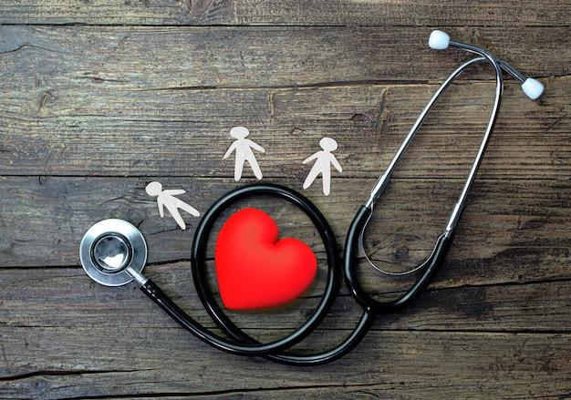 Estetoscopio con hombres de papel y corazón rojo sobre mesa de madera rústica