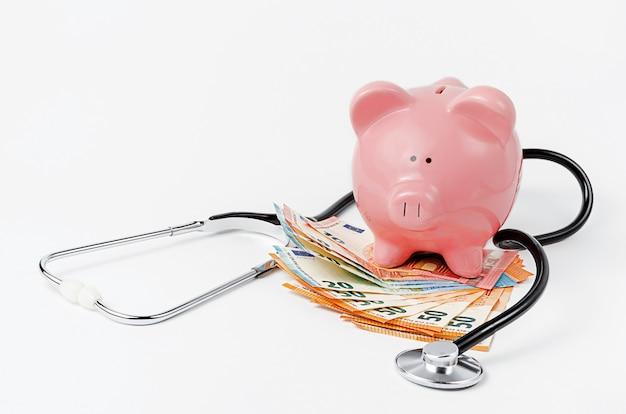 Estetoscopio, hucha y moneda euro en la pared blanca. copia espacio concepto de cobertura de seguro médico