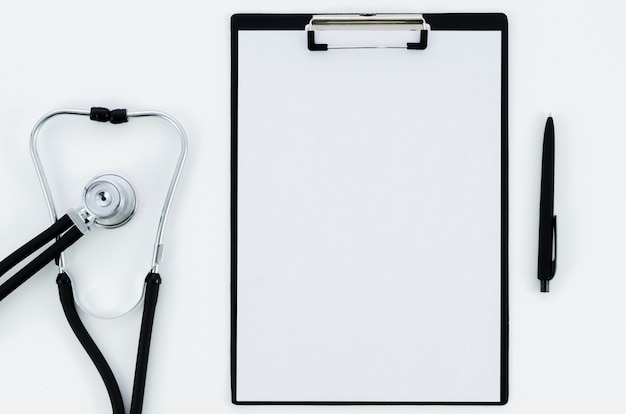 Estetoscopio; libro blanco en el portapapeles con pluma aislada sobre fondo blanco