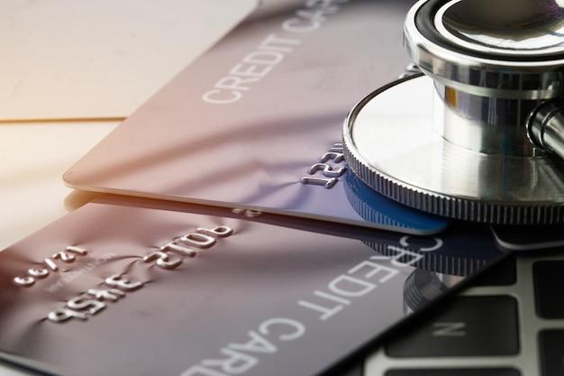 Estetoscopio en maqueta tarjeta de crédito con tarjetahabiente en el escritorio del hospital