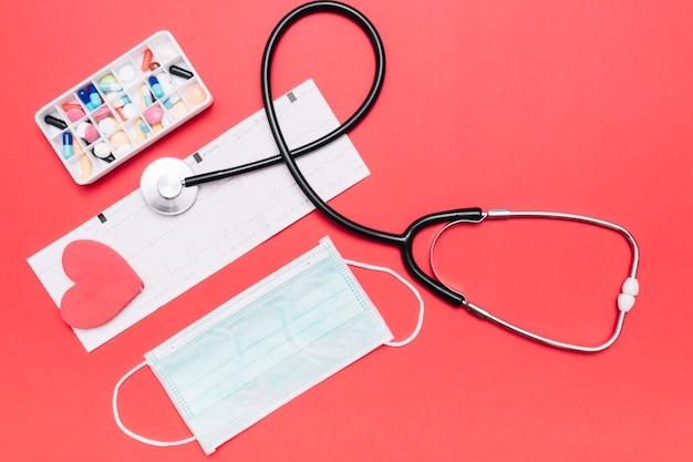 Estetoscopio y máscara cerca de píldoras y cardiograma