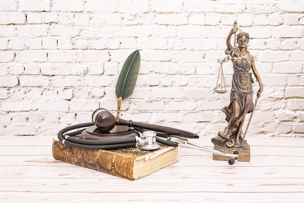 Estetoscopio con mazo de juez y símbolo de la justicia. concepto de lesiones médicas.