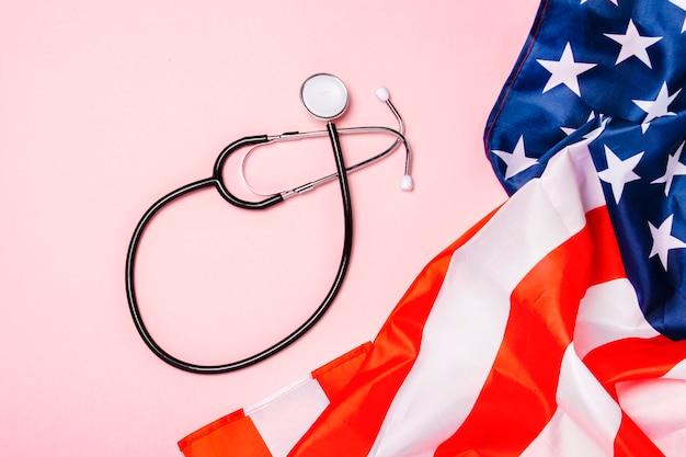 Estetoscopio médico y la bandera de estados unidos sobre una superficie rosa. concepto de salud, medicina, virus, epidemia, alta calidad, el mejor del mundo. vista plana, vista superior