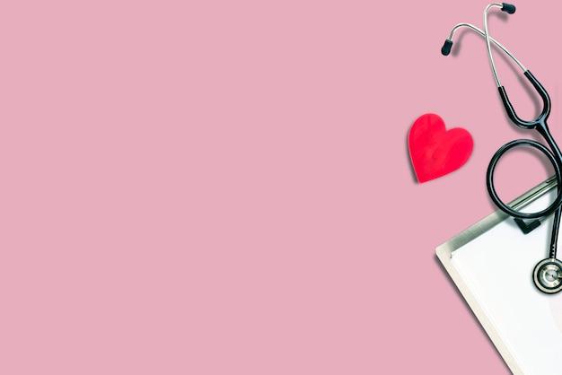 Estetoscopio médico con forma de corazón y cartulina sobre fondo rosa.