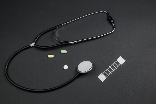 Estetoscopio médico, medicación y termómetro-tira sobre fondo negro aislado