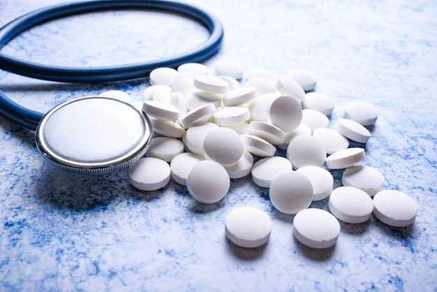 Estetoscopio médico y muchas pastillas blancas superficie azul. concepto de cardiología