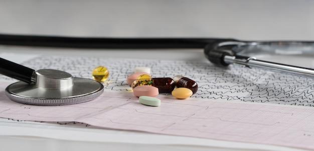 Estetoscopio médico con pastillas y cardiograma sobre un fondo claro
