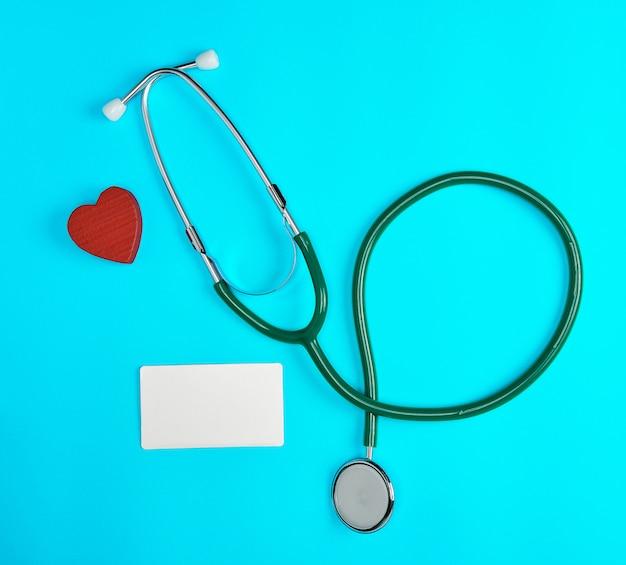 Estetoscopio médico y tarjetas de visita de papel vacías en un fondo azul