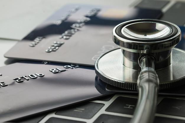 Estetoscopio en mock up tarjeta de crédito con número en la tarjeta en la computadora