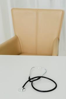 Estetoscopio en la parte superior del escritorio con silla en segundo plano.