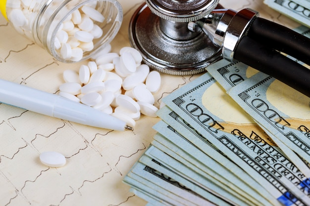 Estetoscopio pastillas y dólares de fondo con pastillas y cardiograma