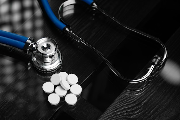 Estetoscopio y pastillas están sobre la mesa negra